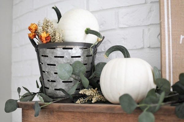Neutral fall decor display of white pumpkins, greenery and an olive bucket.
