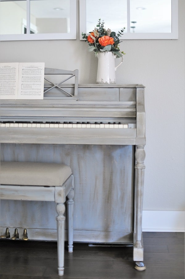 Neutral fall decor bouquet of flowers atop a grey painted piano.