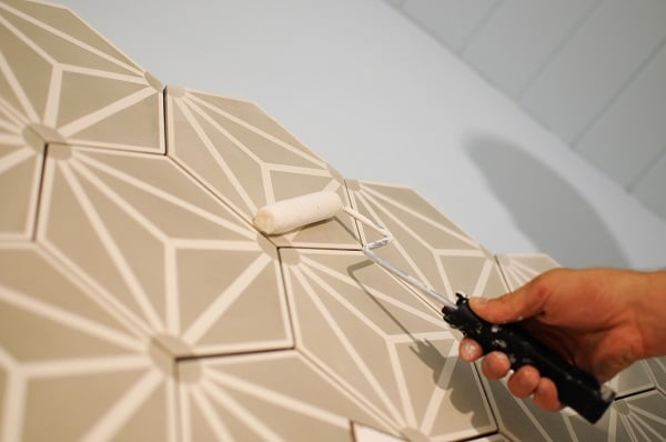 Apply the sealer to your tile accent wall with a roller.