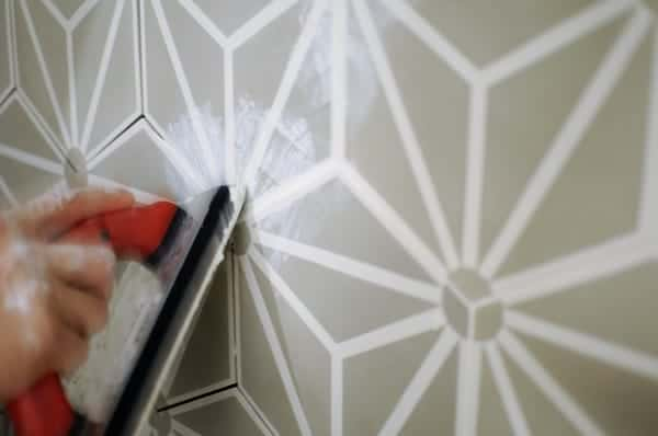 Filling the grout lines on a cement tile accent wall.
