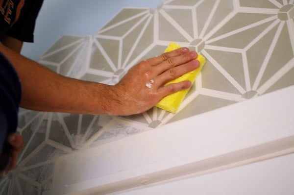Wiping excess grout off the face of a cement tile accent wall.