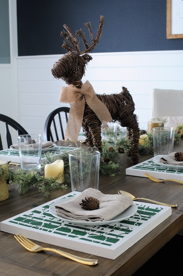 Christmas tablescape with linen napkins, DIY placemats and pine cone place markers.