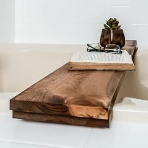 Close up of a DIY wooden bathtub tray with a book, glasses and succulent placed on top of it.