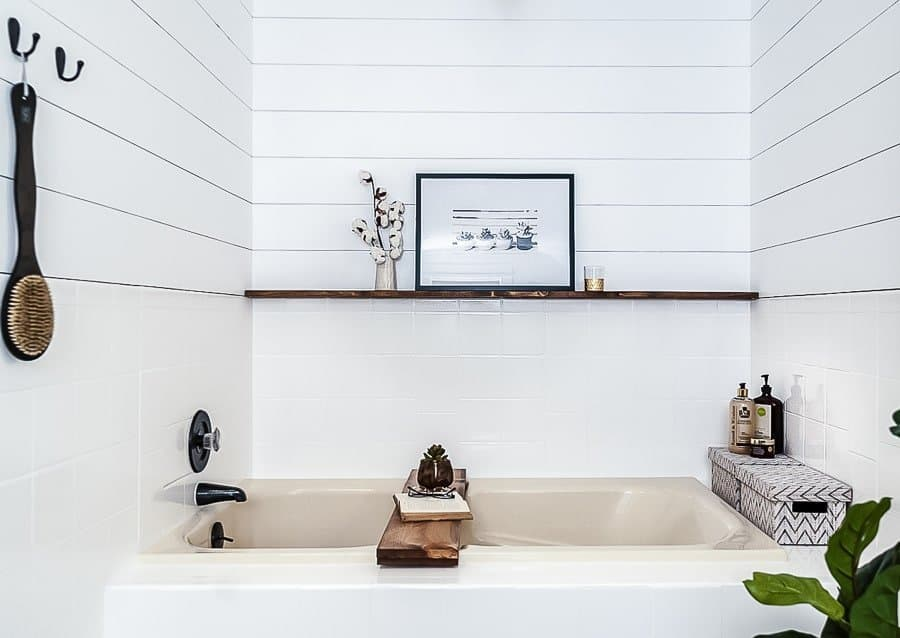 Cream soaker tub with white tile, white shiplap and wooden bathtub tray on top.