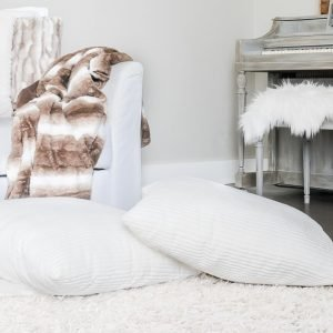 White floor pillows on a cream shag rug in a cozy home for winter.