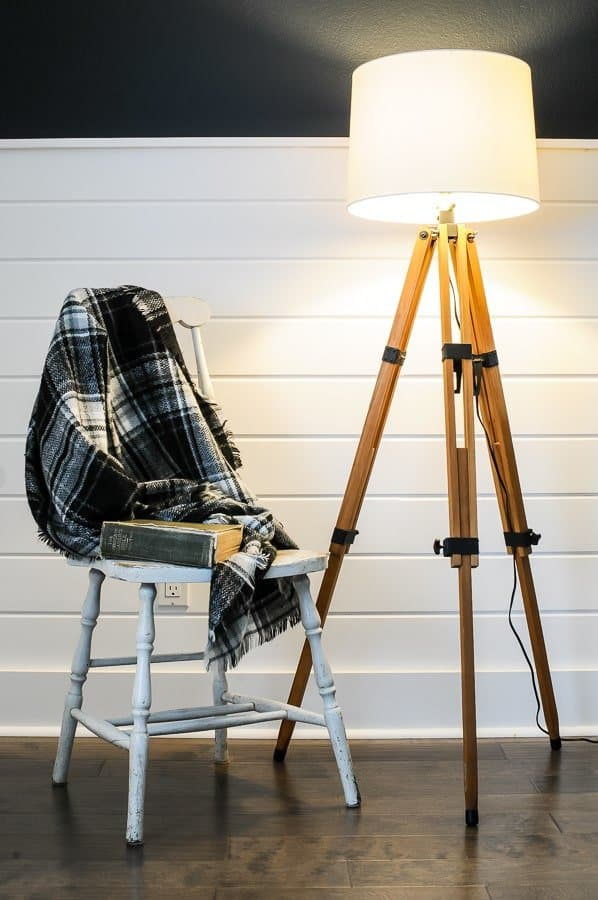 DIY floor lamp made out of a tripod sitting next to a chair with a blanket and book.