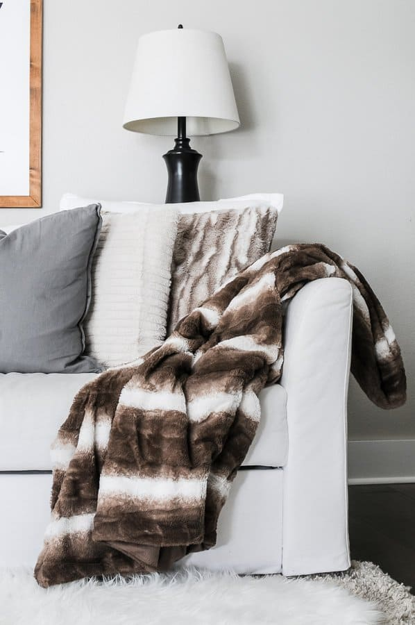 Faux fur blanket draped on a white couch for a cozy home in winter.
