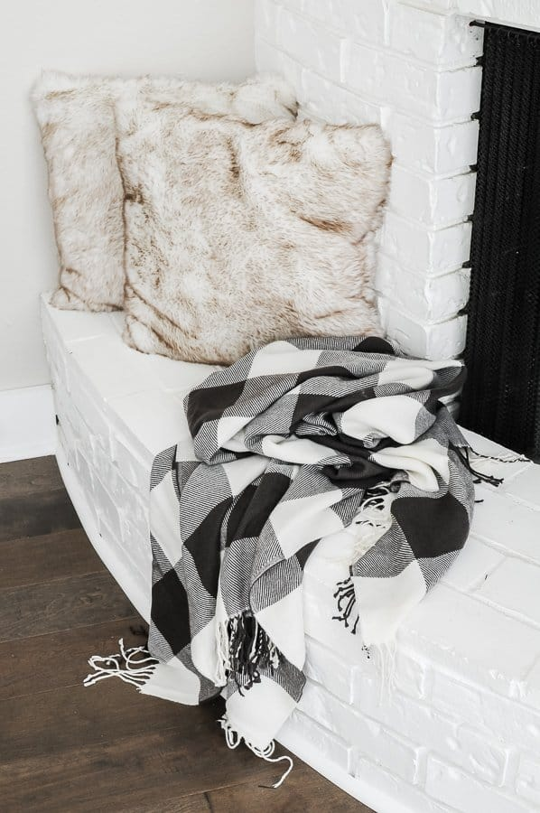 Faux fur pillow and a blanket atop a fireplace hearth for a cozy home in winter.
