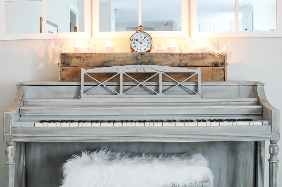 Candles light in a rustic box on top of a chalk painted piano creating a cozy home for winter.