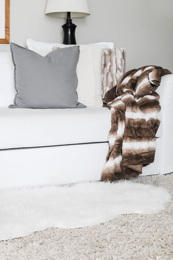 Layered faux fur rug atop a shag rug in a cozy home.