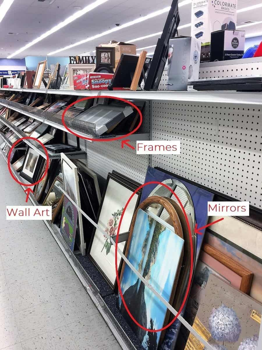 Wide angle of thrift store shelf filled with frames, art and mirrors with items worth looking at circled in red.