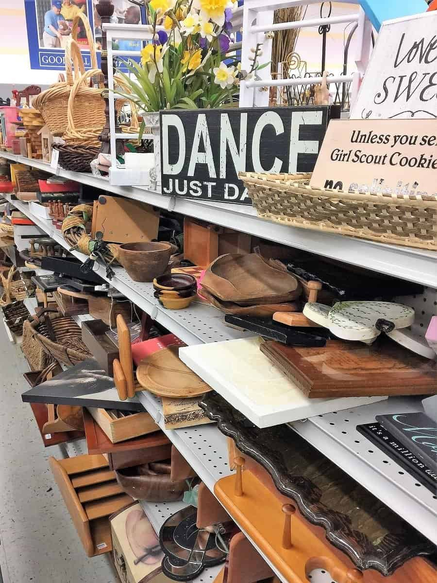 Thrift store aisle with shelves full of wooden bowls, decor and signs.