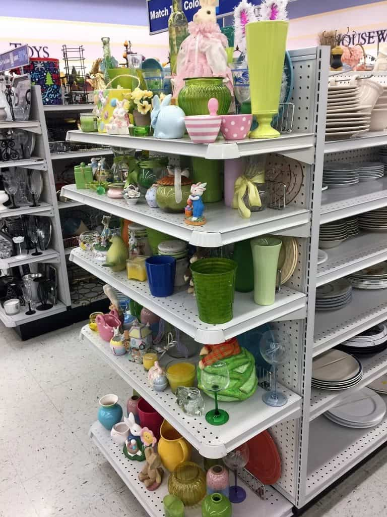 End-cap of thrift store aisle with colorful glassware and figurines.