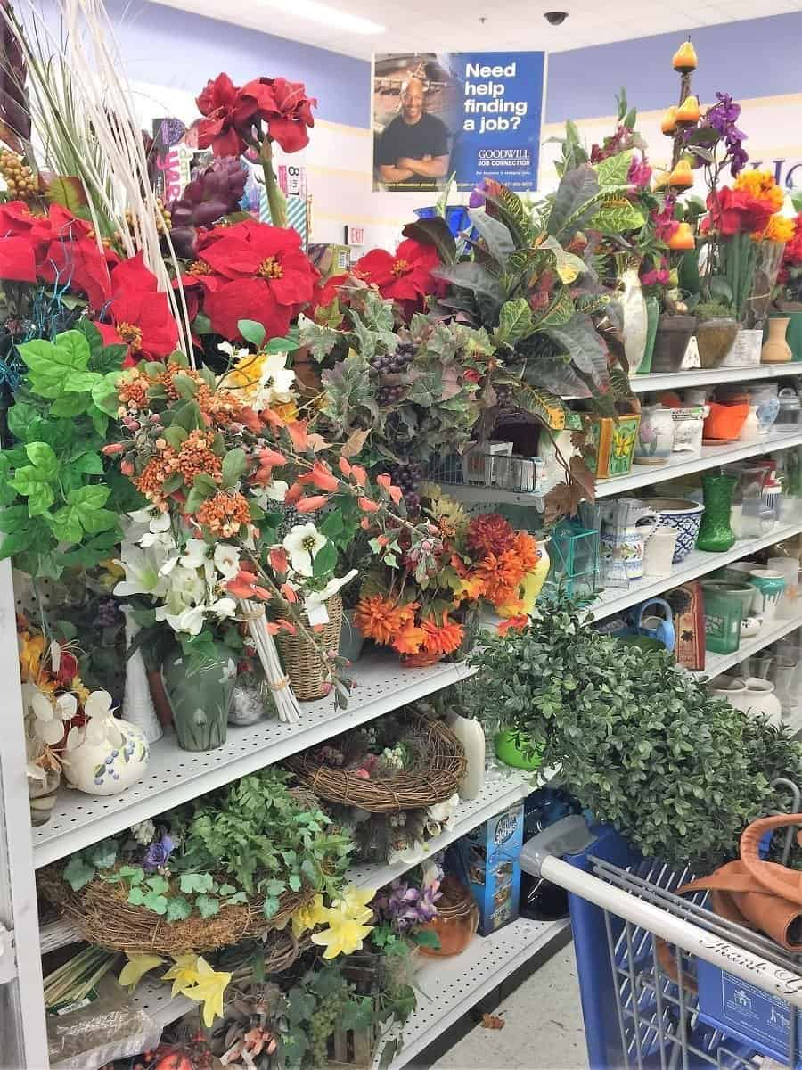 Thrift store aisle with shelves of artificial plants, greenery and pots.