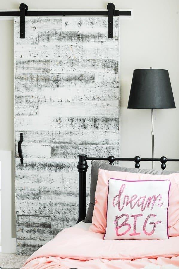 Reclaimed wood barn door in behind a black metal bed with pink linens.