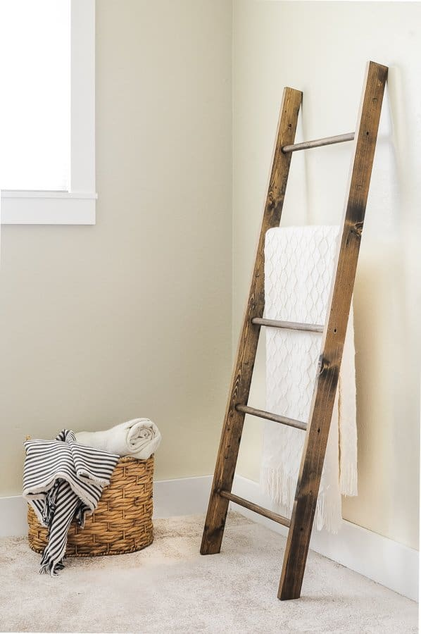 Blanket ladder leaned against a wall with a basket of blankets next to it.