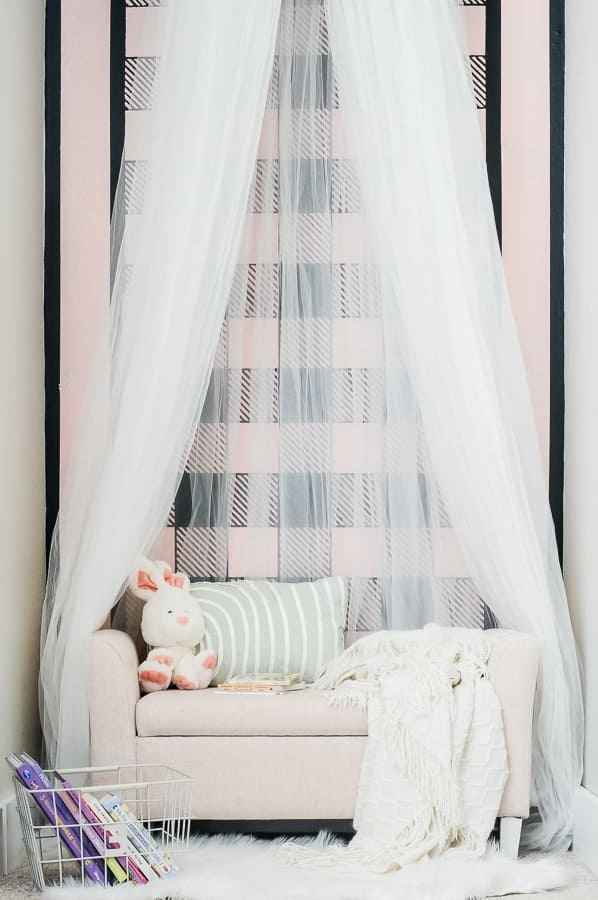 Kid's reading nook with an accent wall, tulle canopy, pink settee and accessories.