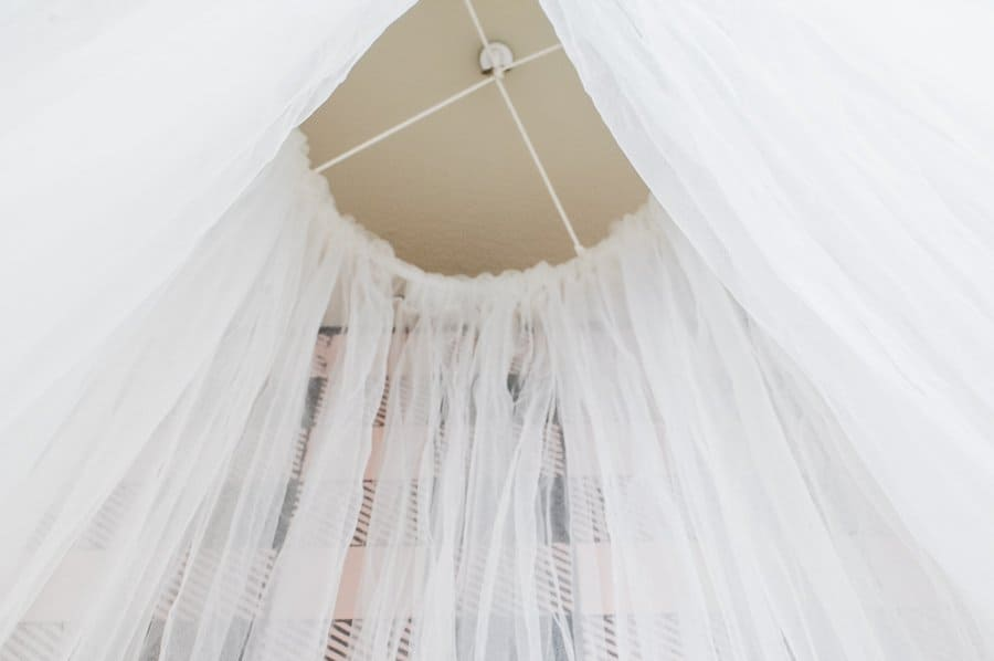 Tulle canopy hooked to the ceiling in a closet kid's reading nook.