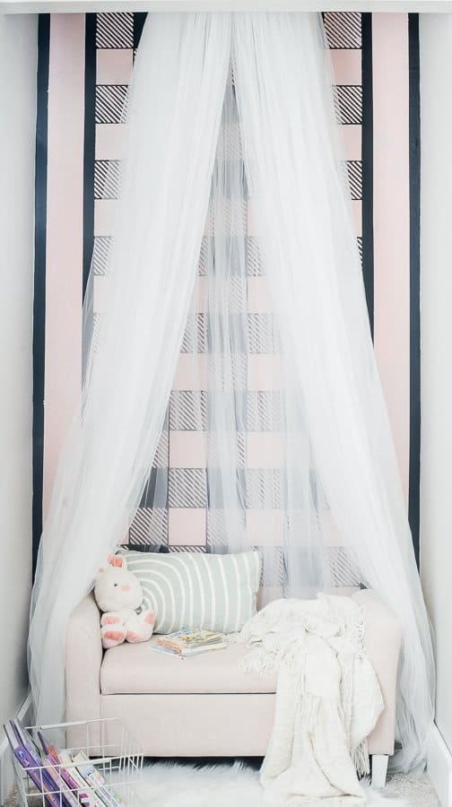Kid's reading nook with a painted accent wall, tulle canopy, pink storage bench and accessories.