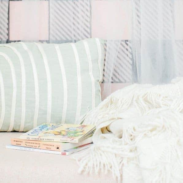 Close up of books, pillow and blanket on a kid's reading nook bench.