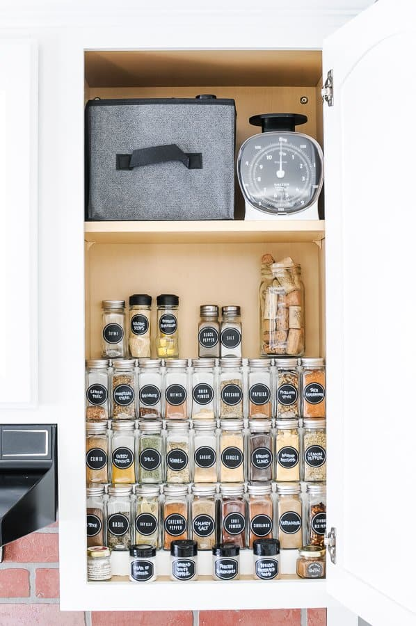 Reveal image of tiered spice organizing spices in a cabinet.