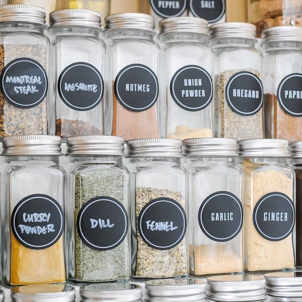 Zoomed in view of glass spice jars for organizing spices in a cabinet.l