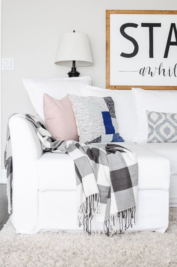 White couch chaise with buffalo check throw and pink pillow in a spring living room.