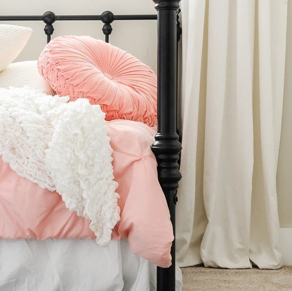 Lots of pillows and long curtains as toddler girl bedroom ideas on a budget.