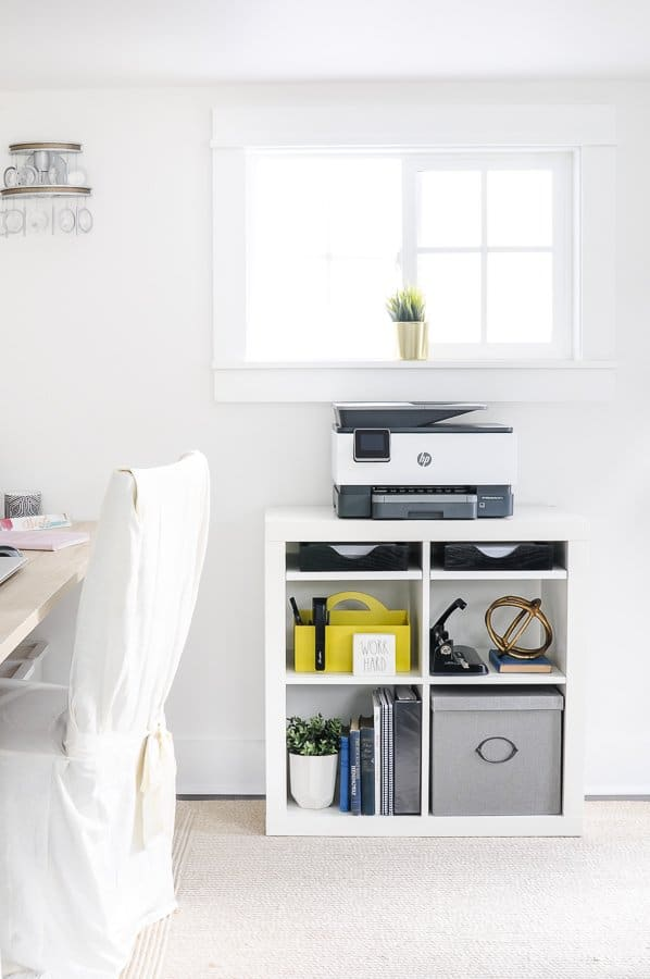 Clean home office with white walls, a linen covered chair, and a white bookcase with a printer on top.
