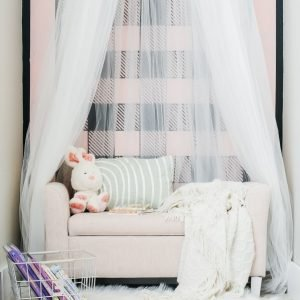 Example of how to make a tulle canopy in a reading nook with pink bench.