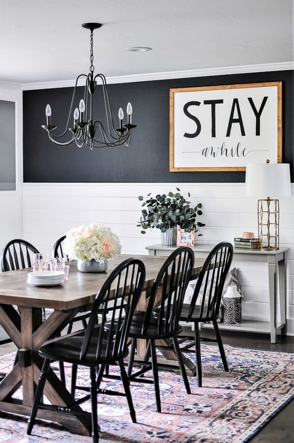 "Dining room with a bright pink rug, a black chandelier and a large farmhouse ""stay awhile"" sign on the wall."