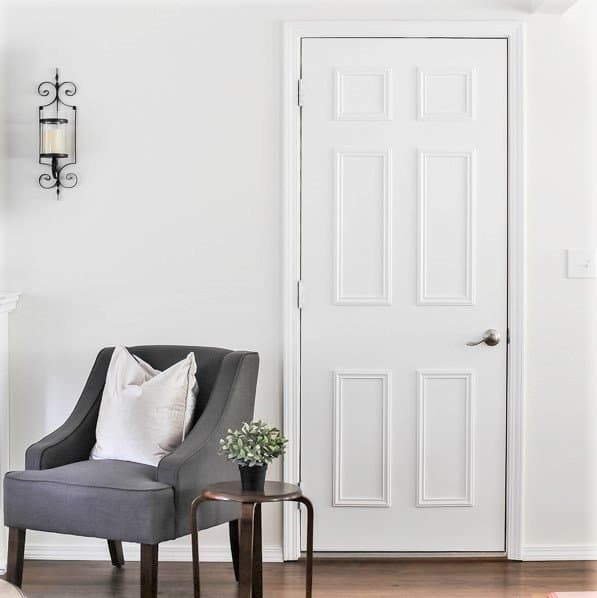Close up of interior door makeover with trim and paint next to a seating area with chair and table.