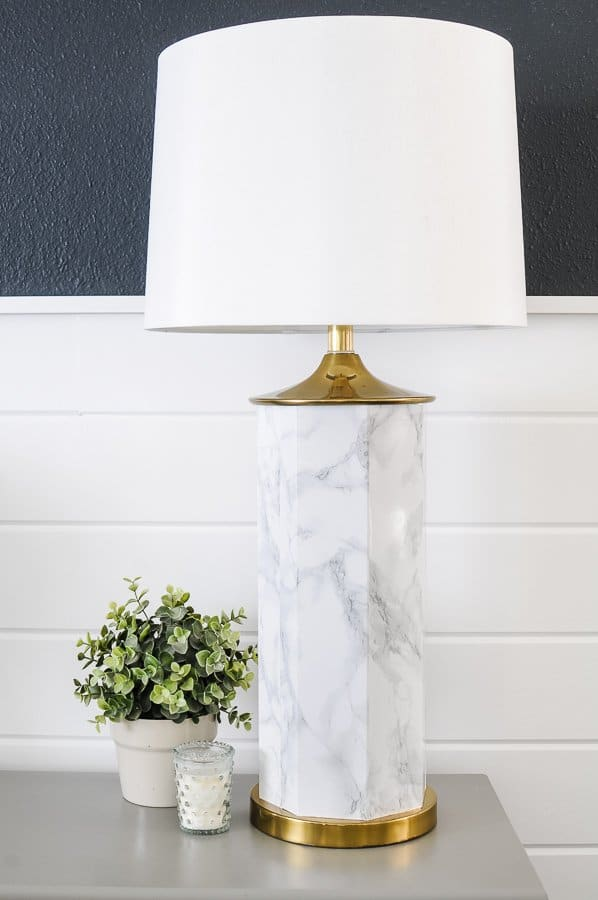 Marble and brass table lamp with a large white shade sitting on a grey table with a plant and candle next to it.