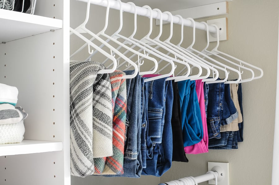 Row of folded pants and scarves hung in an organized closet.