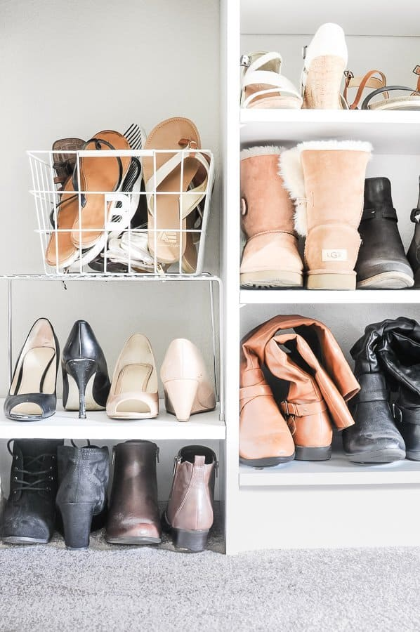 Nicely organized shoes arranged in a basket and on shelves in a decluttered closet.