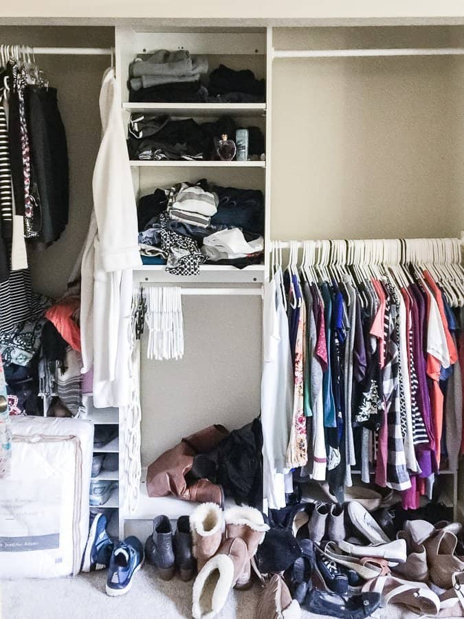 Closet half-full with clothes in the process of being decluttered.