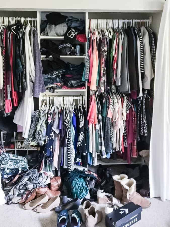 Unorganized and cluttered closet full of clothes and shoes.