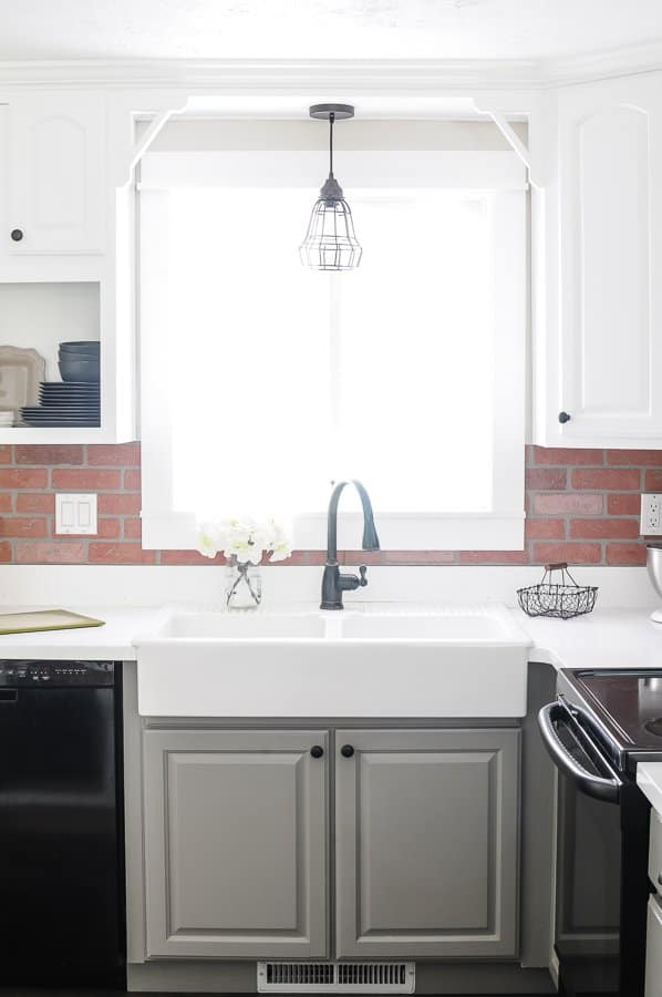Farmhouse apron front sink with industrial lighting and brick backsplash.