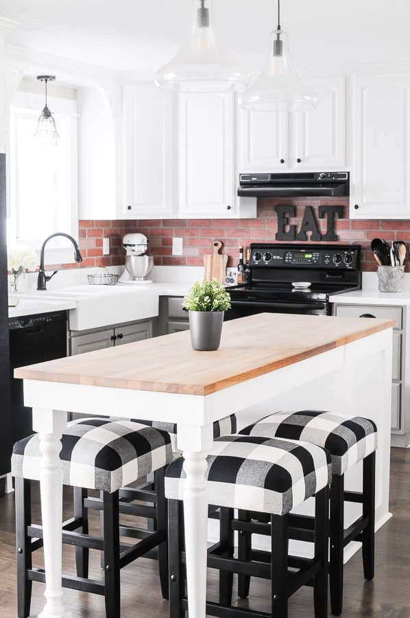 Farmhouse kitchen decorating ideas on a budget - brick backsplash, wood countertops and buffalo check stools!