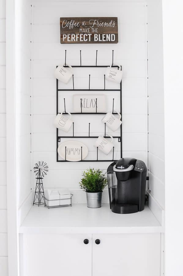 Farmhouse kitchen decorating idea for a coffee station with a wood sign and metal mug rack.
