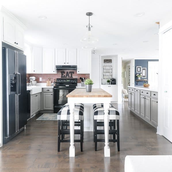 Farmhouse kitchen decorating ideas with two-toned cabinets and buffalo check stools.