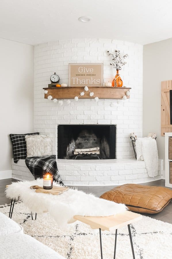 Living room decorated for fall with a white pom pom garland hung on the mantel.