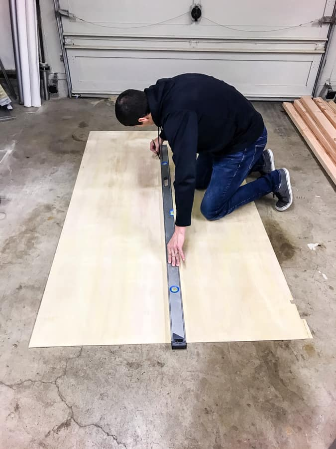 Man standing over a piece of thin plywood marking the center line with a long level.
