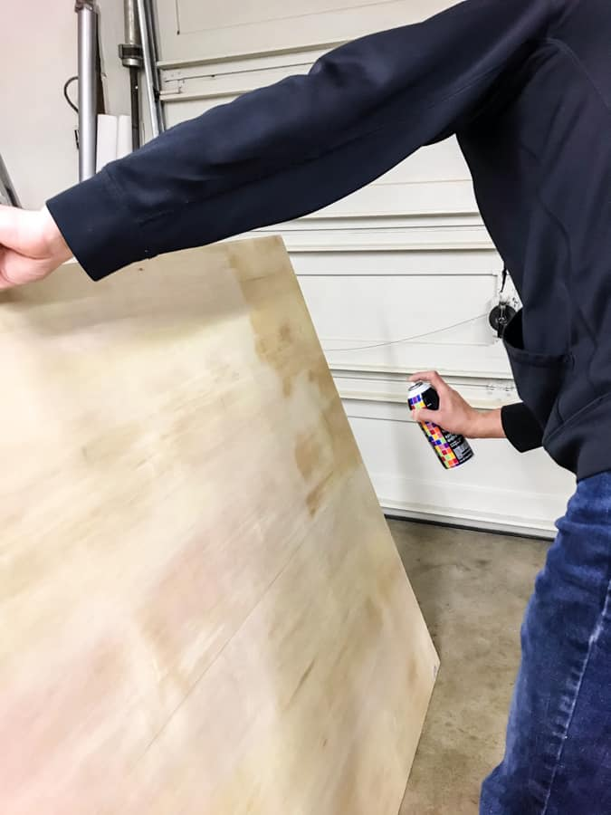 Man spraying adhesive onto thin plywood before sticking on cork for a cork wall.