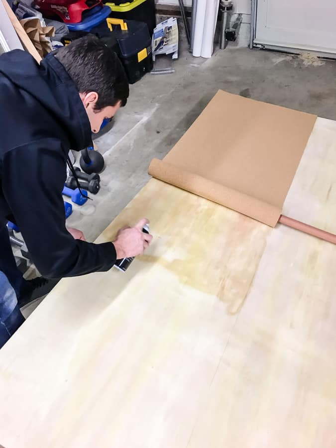 Man spraying a second section of plywood with adhesive to roll and adhere more cork onto it.