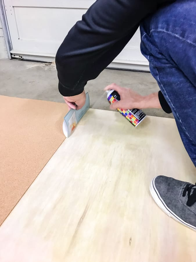 Man spraying adhesive onto plywood against a folded up piece of paper used to protect the cork on the plywood.