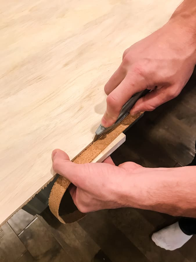 Close up of hands using a box knife to cut away the cork overhang from the edge of the plywood.