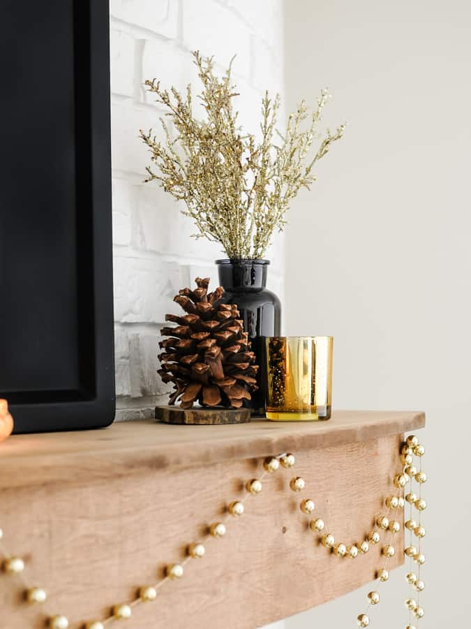 Winter decorations on a mantel with gold stems in a black vase and pinecone.