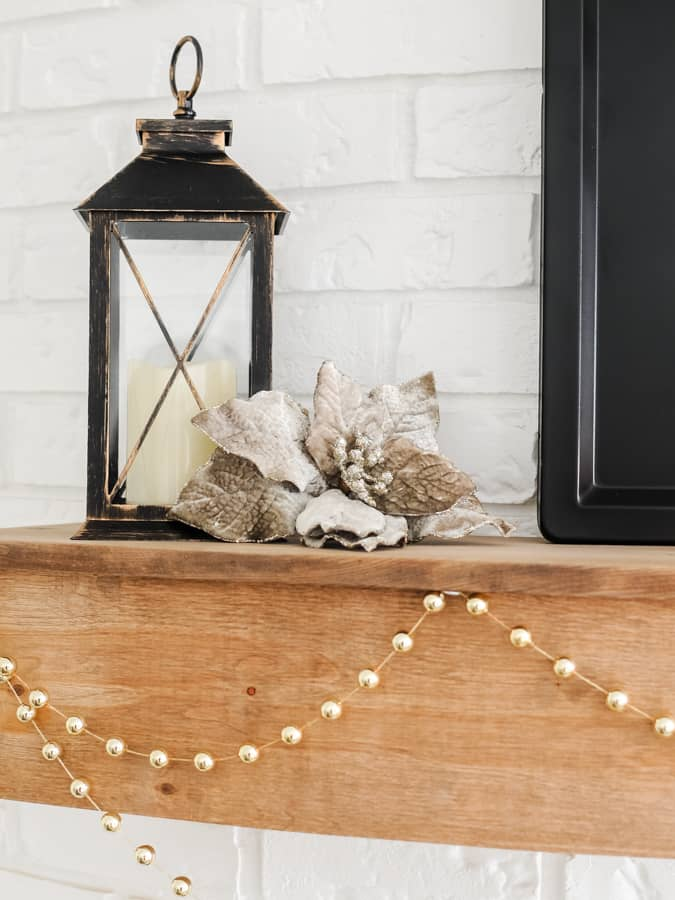 Black lantern and grey flower on a wood mantel with gold bead garland.