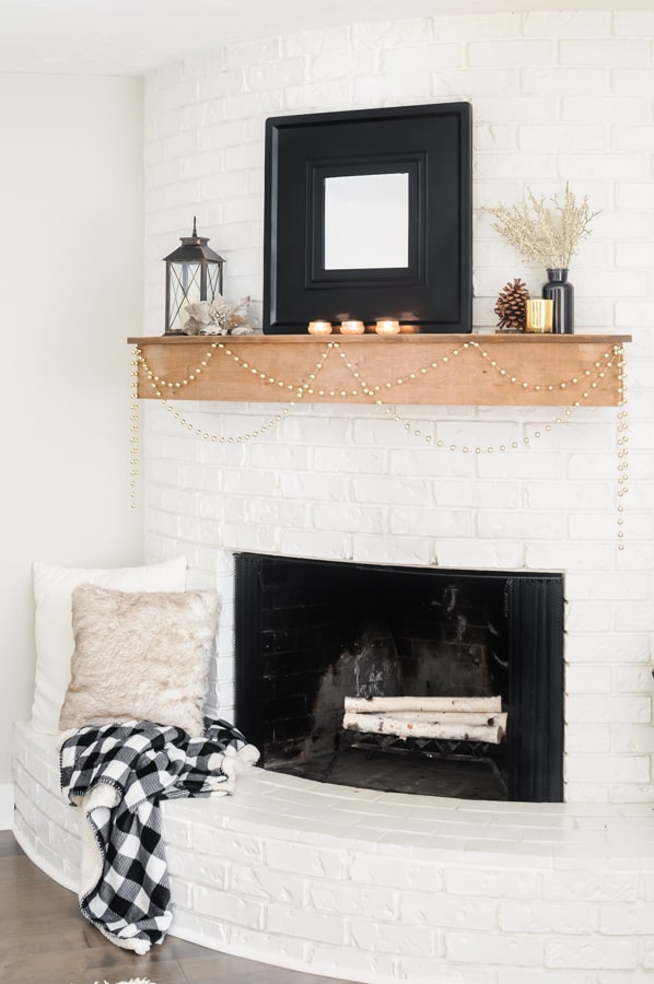 Round, white fireplace with blankets and pillows on the hearth for winter.